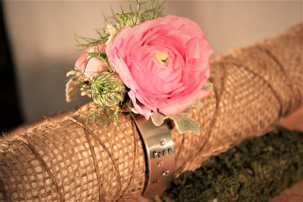 Floral bracelet featuring a personalized cuff, with ranunculus, nigella, dusty miller and lisianthus.