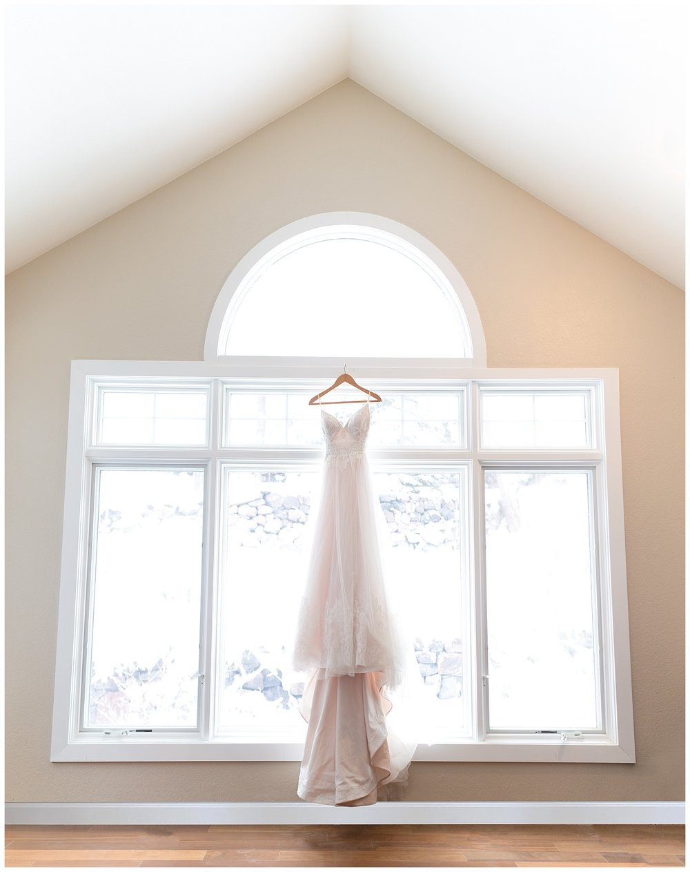 Wedding dress hanging in a brightly lit window