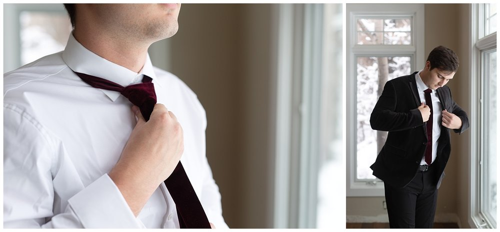 The groom finalizing his look before getting married on a snowy winter day