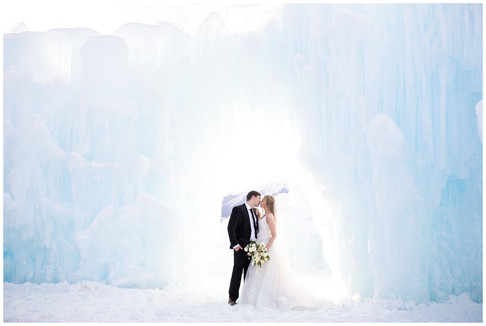 a bride and groom kiss underneath an arch made of ice at the Dillon Ice Castles in Colorado