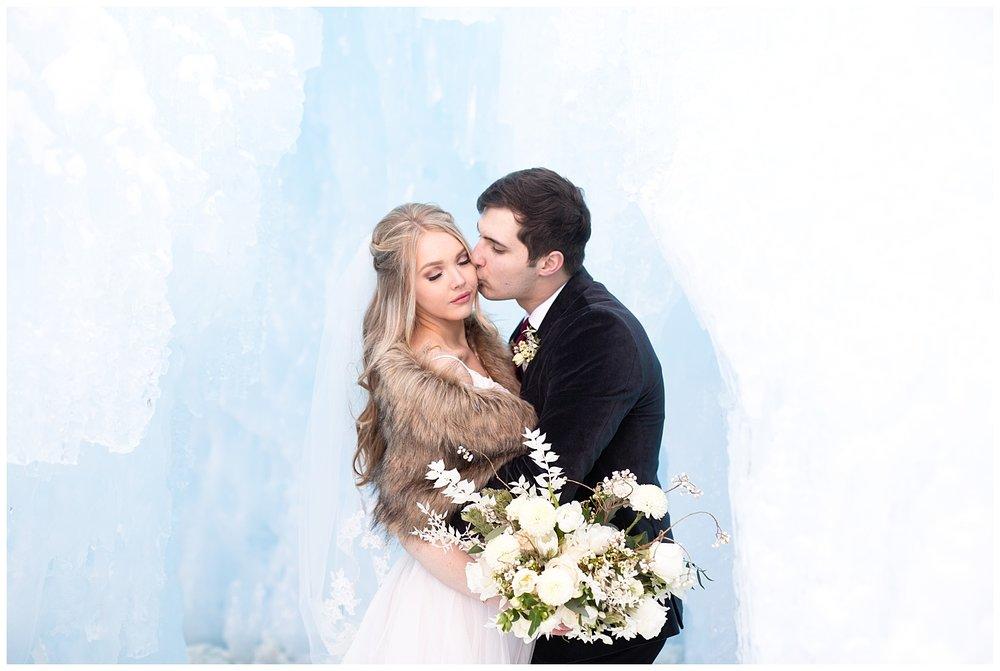 the groom kisses his bride's cheek romantically