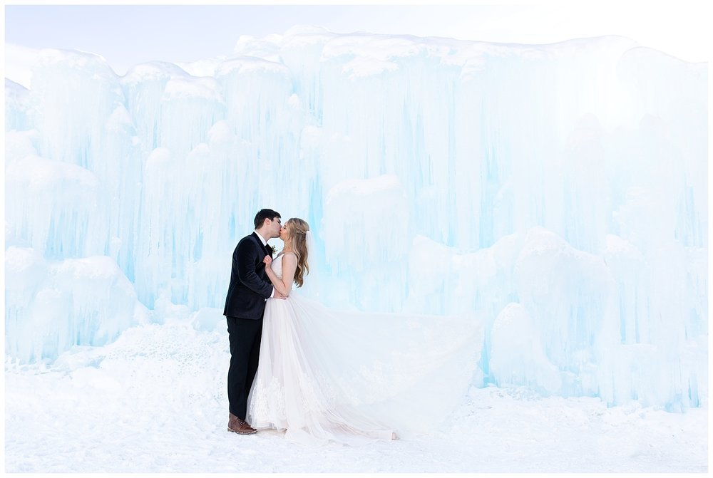 a bride and groom kiss while the bride's dress is flying in the wind at the Dillon Ice Castles