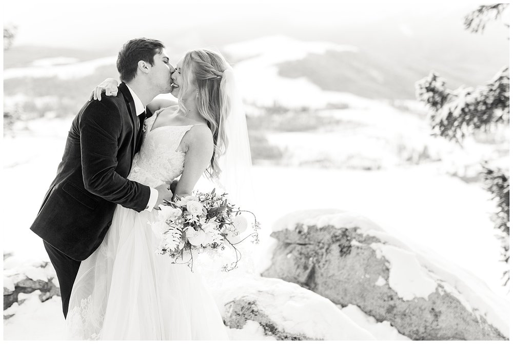A groom helps his bride off of a rock and kisses her while she smiles
