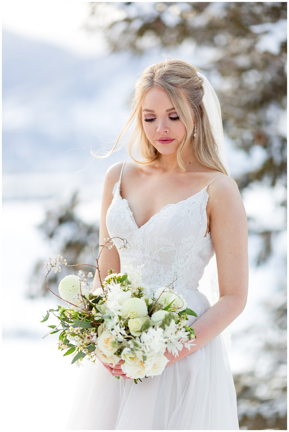 A bride looks down at her wedding bouquet while the wind blows her hair delicately