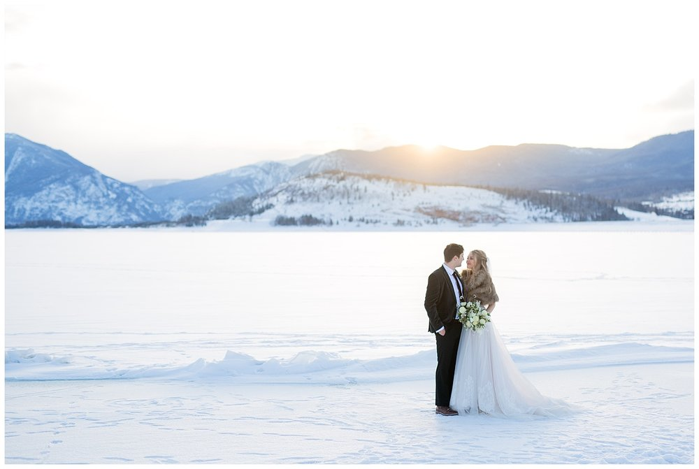 A bride and groom on a frozen lake while the sun is setting behind them