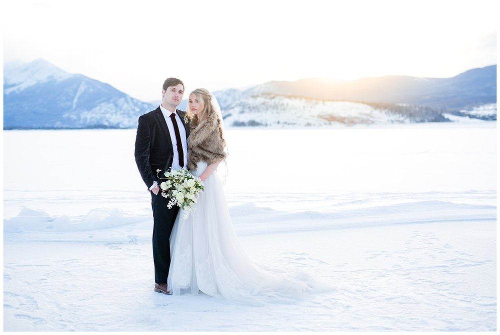 A bride and groom looking straight at the camera in a winter photoshoot