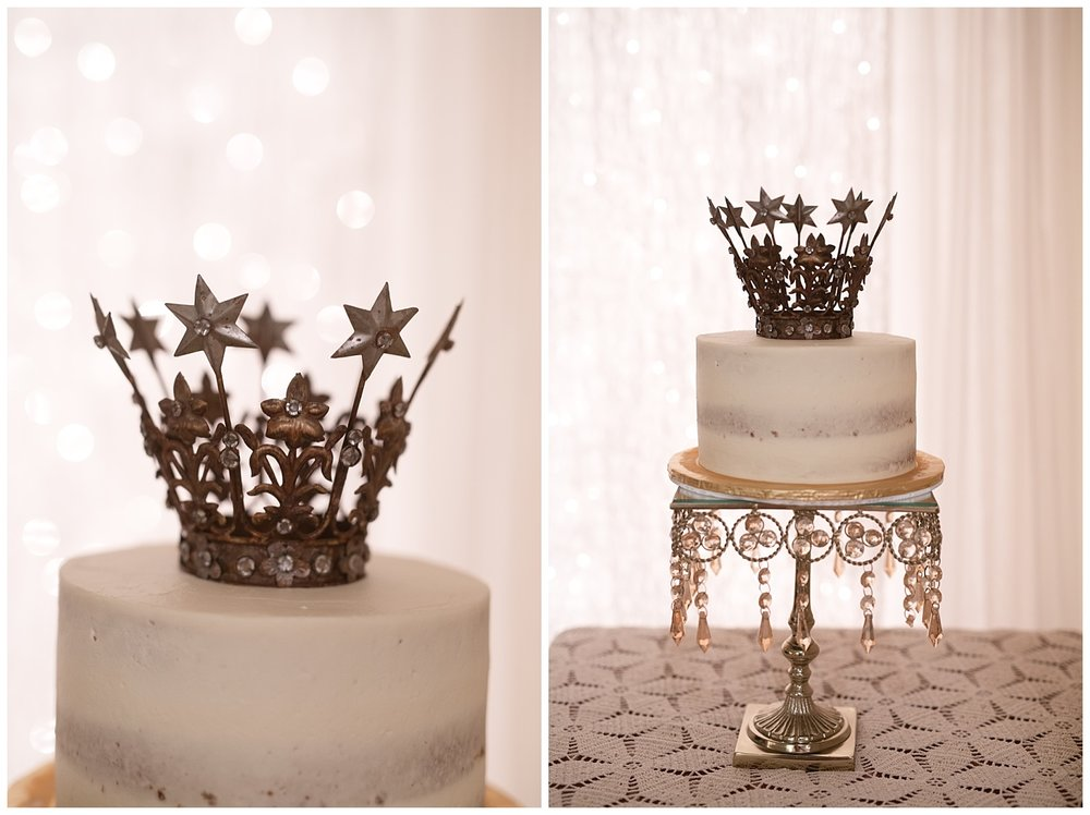 A white semi-naked cake with a crown decoration on top of it