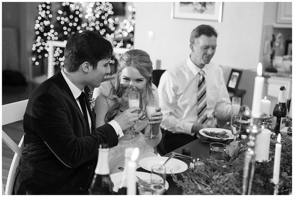 A bride laughs as she clinks glasses with her groom