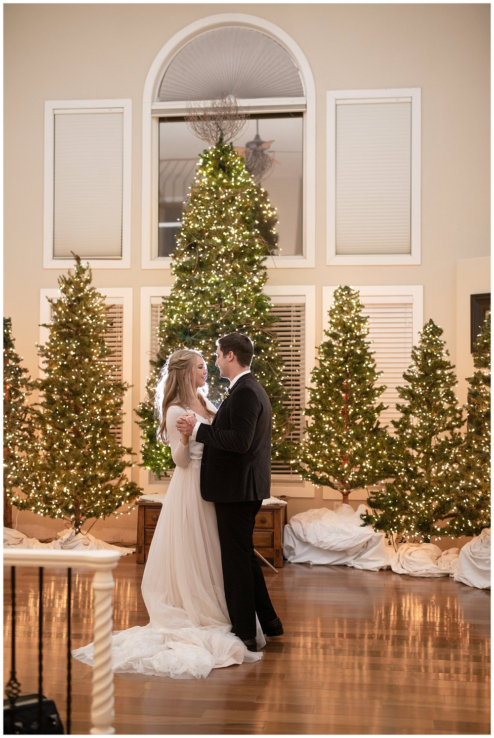 The bride and groom share their first dance surrounded by Christmas trees