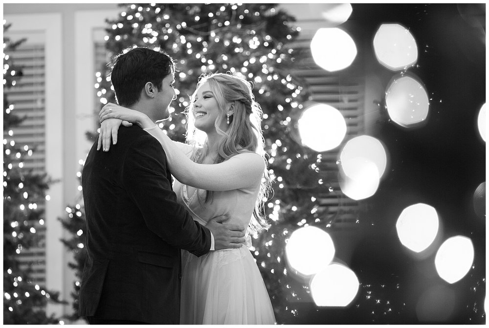 The bride is beaming at her husband while they dance in the middle of Christmas trees