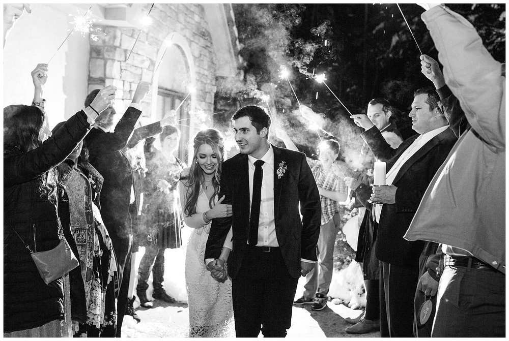 All of the wedding guests cheer for the bride and groom during their sparkler exit