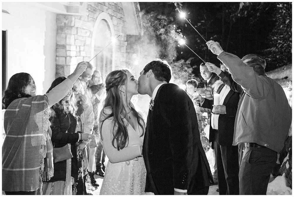 The bride and groom share their last kiss of the evening while the guests all hold sparklers