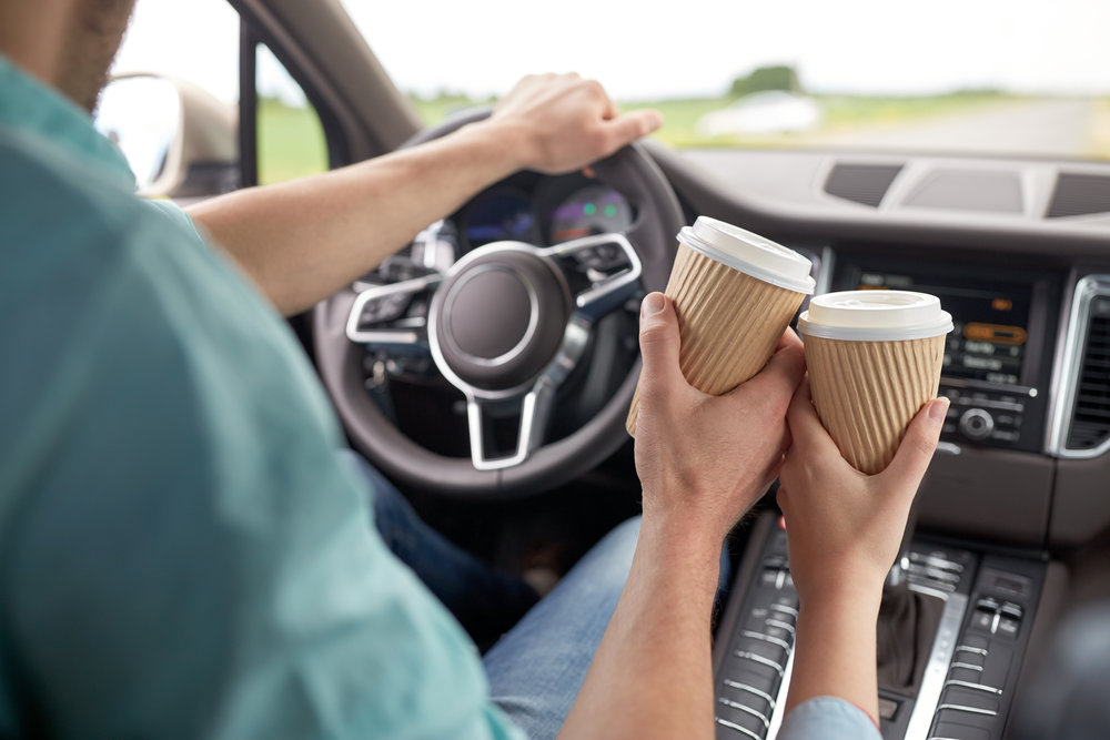 close-up-of-couple-driving-in-car-with-coffee-PSM5DJQ.jpg