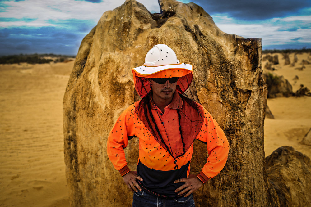 A miner is covered in flies in Australia and Canada