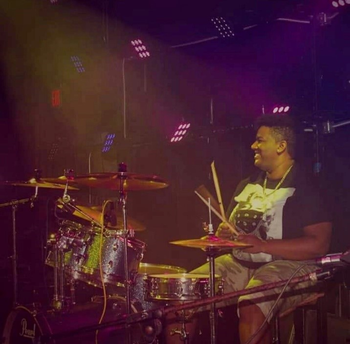 Volunteer of the Year, Eden Corbitt, behind a drum set.