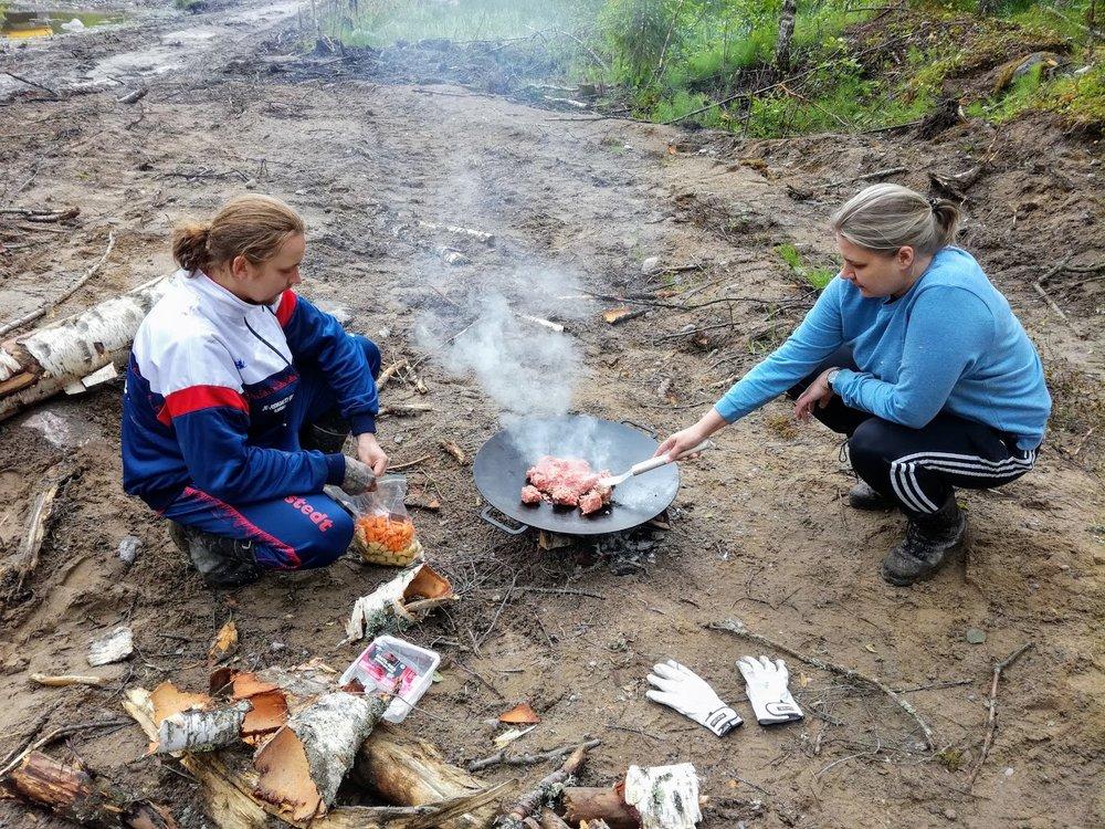Talkoolaisia Helsingistä. Ruoka maistuu todella hyvältä ulkoilmassa. Tässä vaiheessa ei vielä ollut vakituista grillipaikkaa, vaan nuotio tehtiin sinne, missä satuttiin olemaan nälän yllättäessä.