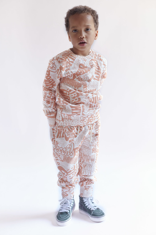 Oskar is 105 cm and wears 104/110 cm size Marius Sweatshirt and Patti Sweatpants in Text print Orange