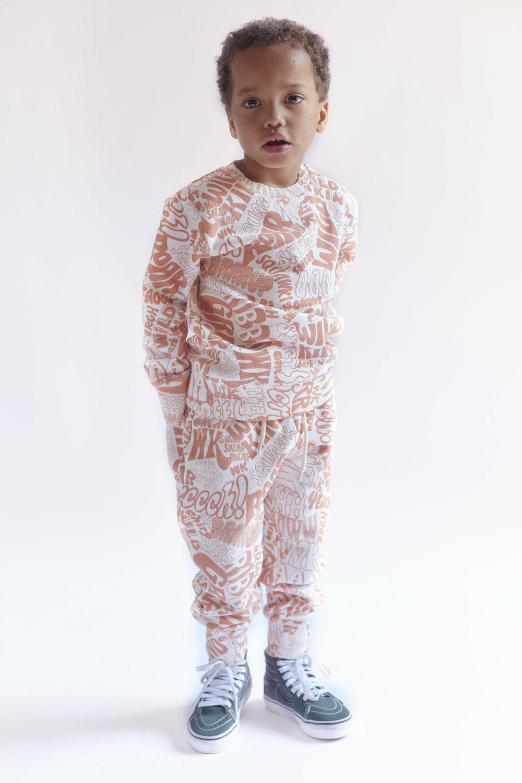 Oskar is 105 cm and wears Marius Sweatshirt and Patti Sweatpants Text print Orange in size 104/110