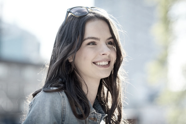 Young lady smiling in the sun after cosmetic dentistry consultation