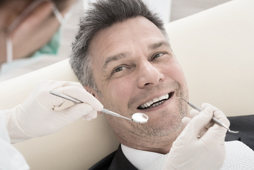 Dentist in Woking examines patient's tooth cavities and suggests inlays and onlays