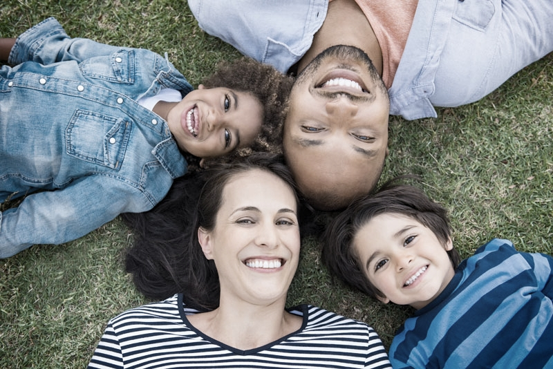 Family smiling and lying on grass after new patient examinations