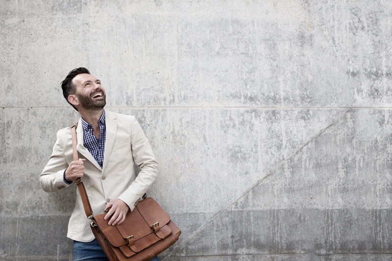 Attractive man with leather bag is smiling after becoming a new dental patient