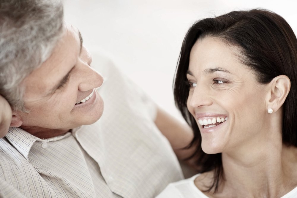 Couple in their 50s smiling after dental crowns