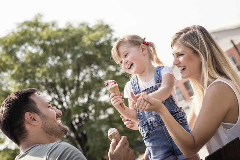 Young girl enjoys ice cream in the park with her parents following children's dentistry appointment