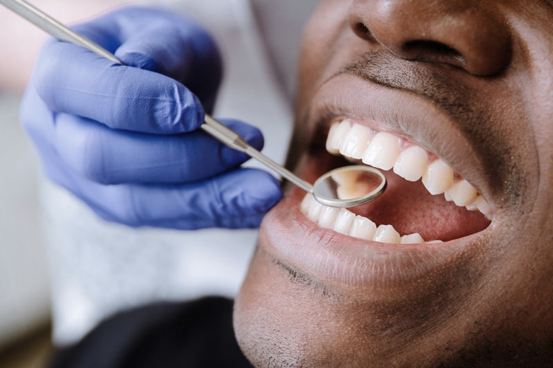 Close-up of dentist examining man's mouth for tooth decay