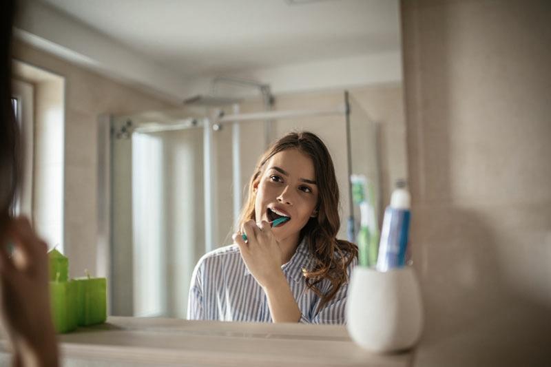 Lady brushing teeth in mirror as part of dental hygiene routine