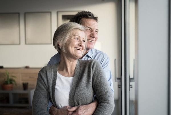 Senior couple smiling after dental implants in Woking