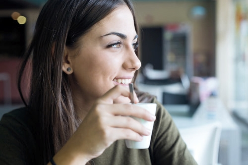 Young woman enjoys her coffee following general dentistry check-up in Woking