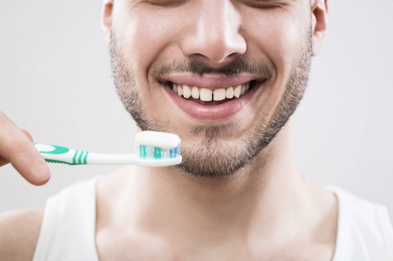 Man holding toothbrush after advice from dental hygienist in Woking