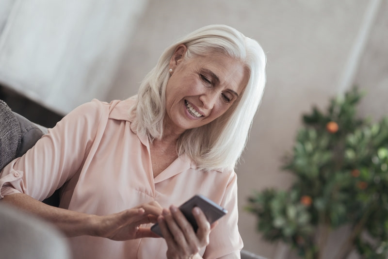 Lady in her 60s on her phone and smiling following dental implants