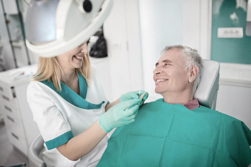 Older male patient in dentist chair discussing dental implant treatment