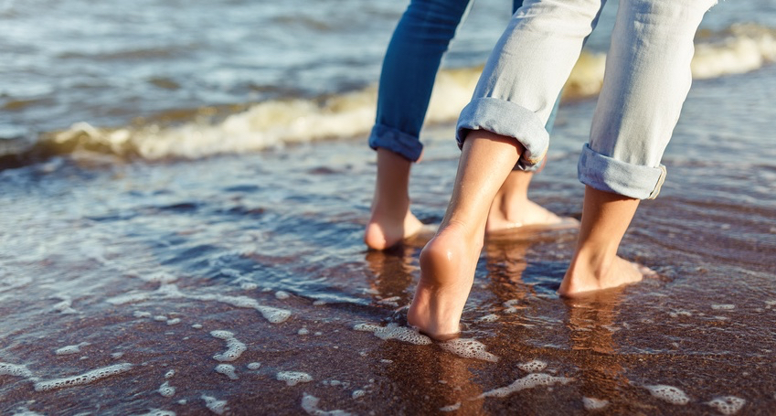 feet-of-couple-woman-and-man-in-the-sea-waves.jpg