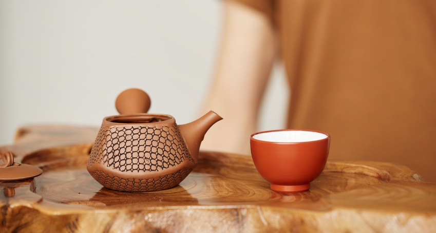 Young-man-sitting-in-meditation-pose-in-front-of-tea-set.-Relaxation-concept.jpg