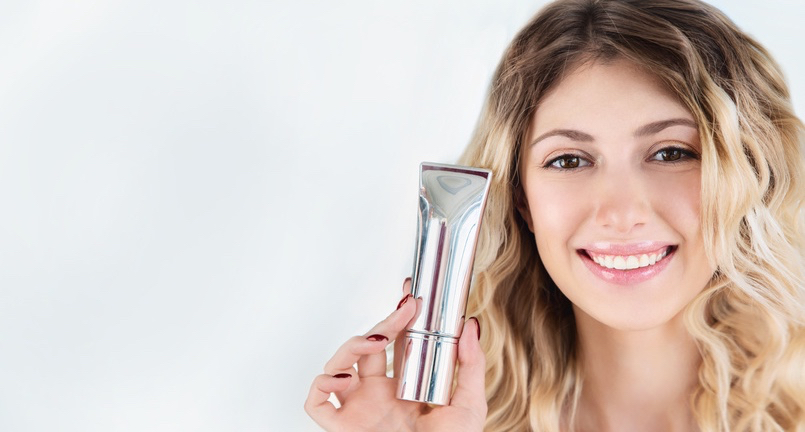 Beautiful-smiling-girl-with-wavy-hair-holds-of-silver-tube-of-moisturizer-oil-wellness-exfoliator-peeling-cream-or-gel-in-hand..jpg