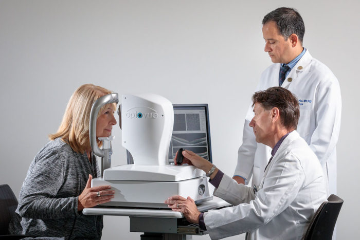 Gregory Van Stavern, MD, (seated) and Rajendra Apte, MD, PhD, examine Kathleen Eisterhold's eyes, using technology that one day may make it possible to screen patients for Alzheimer's disease during an eye exam. In a small study, the eye test was able to detect the presence of Alzheimer's damage in older patients with no symptoms of the disease.