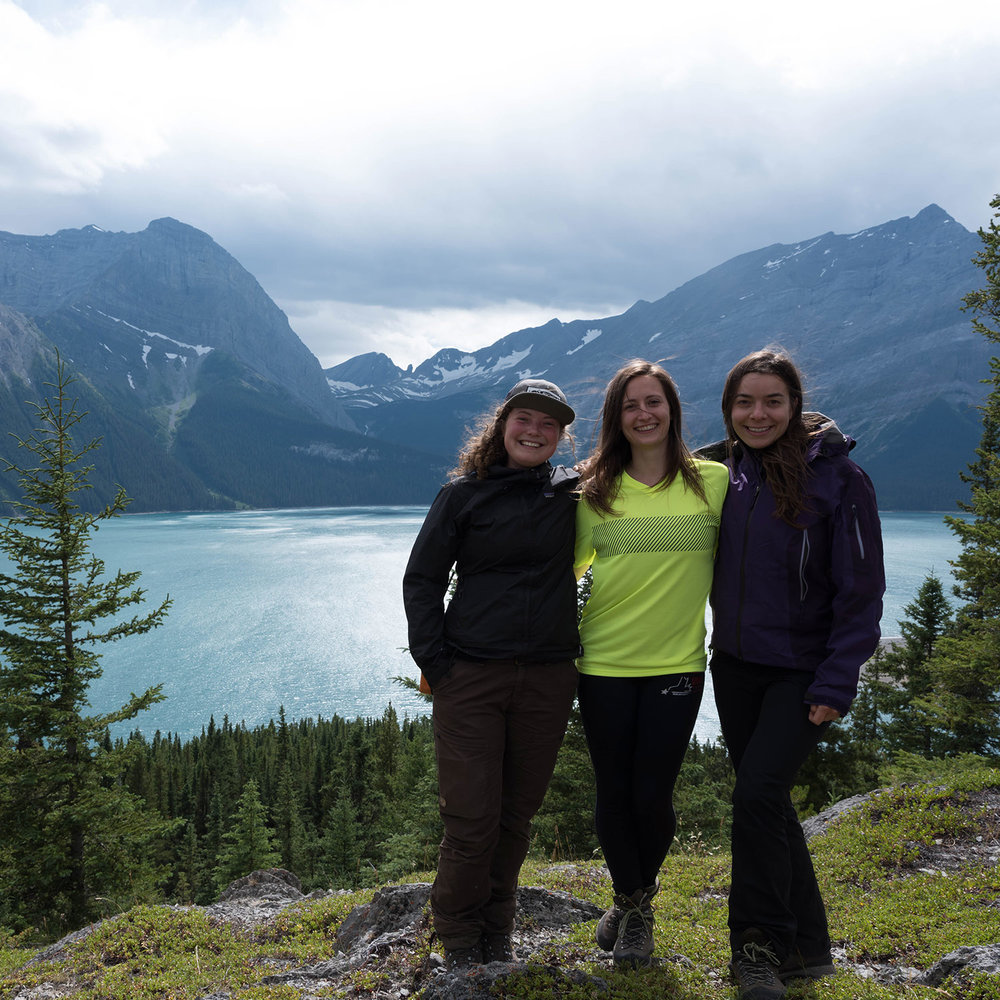 Navarana, Julie, and Sandra stop for a photo near a clear lake in the Rockies.