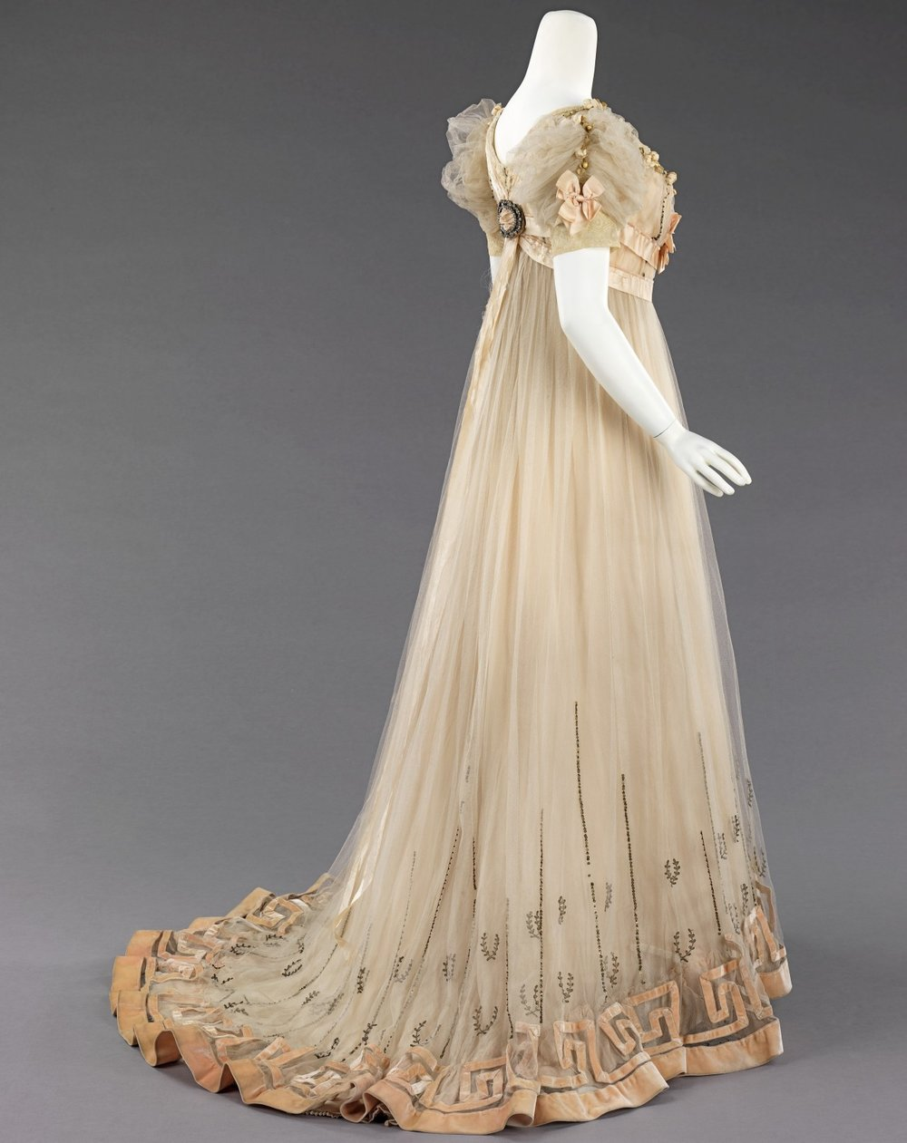 fashioninhistory :       Evening   Dress       House of Paquin       1905-07      Produced several years prior to the 1908 Hellenic designs of Paul Poiret, the raised waist and decorative references to Greek antiquity indicate this classical aesthetic and change of silhouette were in the air from 1905 on. As the leading house of couture druing the Belle Epoque, Paquin's promotion of this line would have been widely known to the public. The dress also incorporates signature decorative techniques such as velvet piping outlining peach satin ribbon at neckline and waist and the contrasting tones and reflections of silver, satin and velvet.  The Metropolitan Museum of Art
