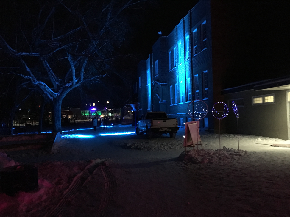 "Rutherford School lit up with changing coloured lights, used as ""warming station"" for people about to head down to the Ravine trails."