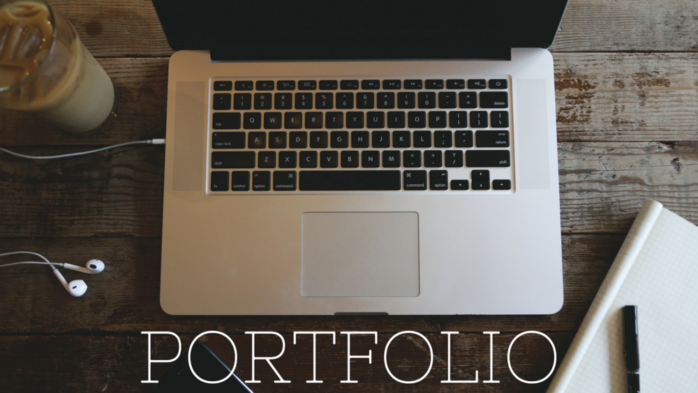[Image: Portfolio in white capital letters at the bottom of the image; the rest of the image has an open Macbook laptop, an open notebook and pen, earbuds, and an iced coffee all on a wooden table]