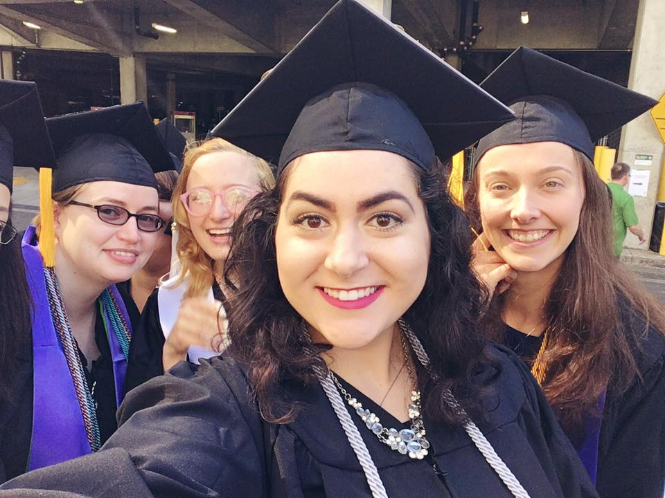 [Image: Alexandria centered in black graduation robes. In the background are several of her PSU WGSS cohort members from PSU's 2016 Commencement Address]