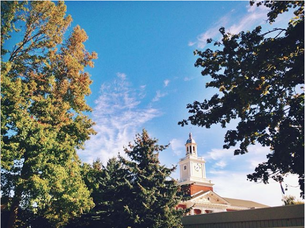 [Image: Bell tower of Roosevelt high school in the bottom center of the image, with full trees in the foreground]