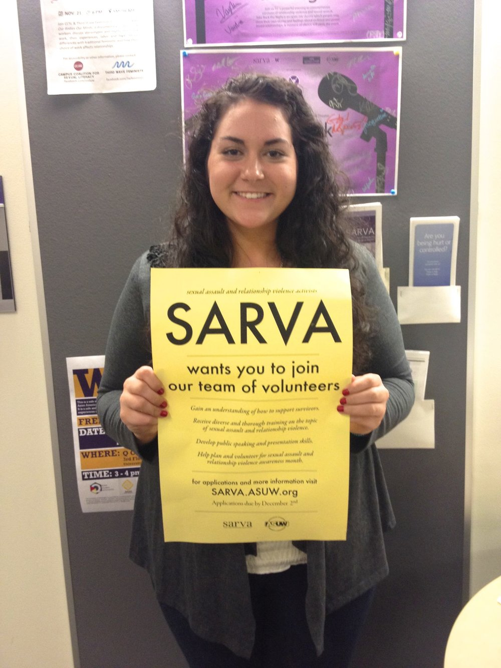 [Image: Alexandria holding a yellow ASUW SARVA sign to prompt volunteers to join the community (2013)]