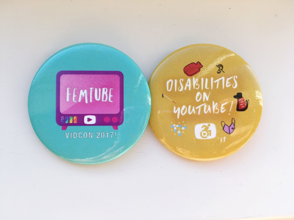 [Image: close-up of two buttons; left--blue button with pink TV background and white capital letters, FEMTUBE VIDCON 2017; right-- yellow button with various icons of disability related items, and white capital letters, DISABILITIES ON YOUTUBE!]