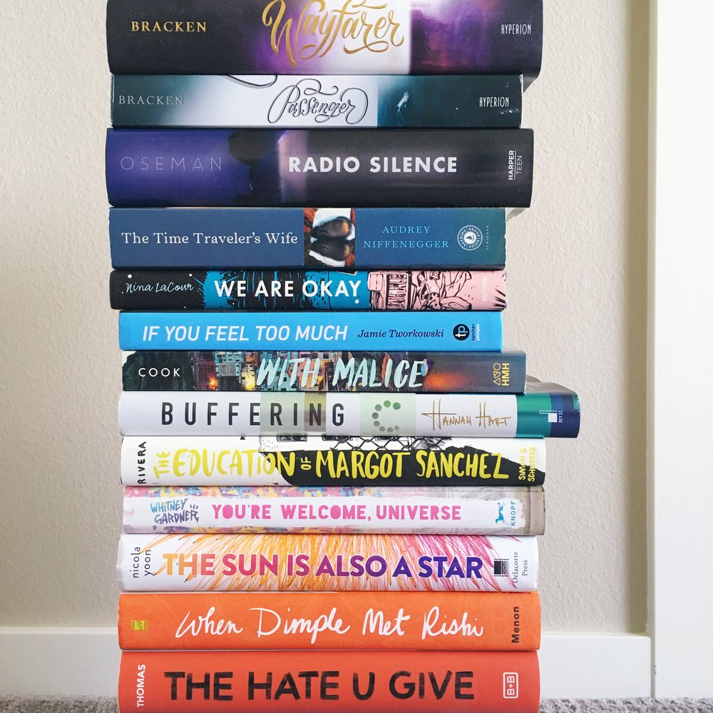 [Image: vertical stack of hard-copy books, including from bottom to top: The Hate U Give; When Dimple Met Rishi; The Sun Is Also a Star; You're Welcome, Universe; The Education of Margot Sanchez; Buffering; With Malice; If You Feel Too Much; We Are Okay; The Time Traveler's Wife; Radio Silence; Passenger; and Wayfarer]