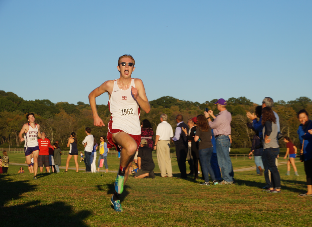 TONGUE OUT  : Isaac Wills runs to the finish line at the end of the City meet.