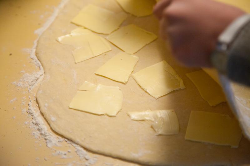 Kun taikina on kerran kaulittu, veistele juustohöylällä voisiivuja toiseen puoleen, käännä ja kaulitse uudestaan.